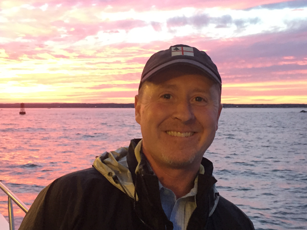 Mike Carroll smiling with sunset-water behind him